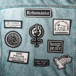 "back of jean jacket with black-and-white progressive patches such as ""end police burtality"" and ""rehumanize"""
