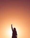 Silhouette of a woman with a raised fist against sunset